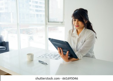 Young woman using digital tablet at desk, indoors by window. young adult arabic pretty 20 years old