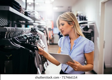 Young woman using digital tablet while shopping in the clothing store.