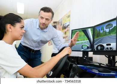 young woman using driving simulator