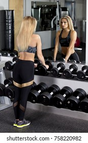 Young woman using dumbbells at gym