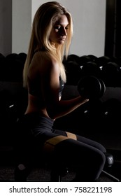 Young woman using dumbbells at gym Selective lighting for effect