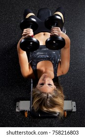Young woman using dumbbells while laying down on a bench at gym