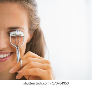 Young woman using eyelash curler
