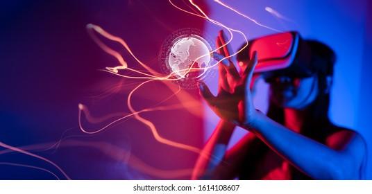 Junge Frau, die eine Brille virtueller Realität auf dunklem Hintergrund verwendet. Smartphone mit VR Headset, Virtual Reality, Zukunftskonzept.Asiatische Frau mit VR Brille in bunten Neonleuchten.