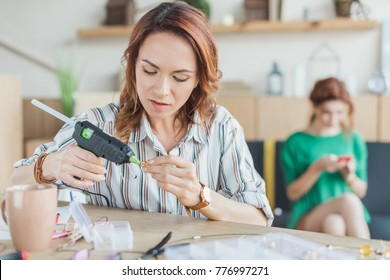 young woman using glue gun in handmade accessories workshop