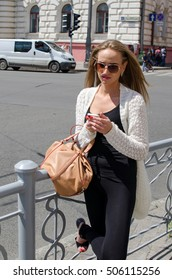 Young woman is using her cellphone on the street