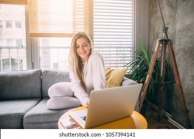 Young woman using her laptop while relaxing on sofa