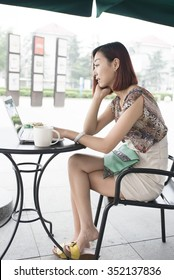 Young woman using her laptop sitting in outdoor cafe