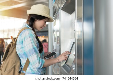 young woman using her phone pay to buy high speed rail train ticket in the station hall. online travel vacation concept.