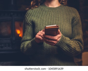 A young woman is using her smart phone by the fire of a log burner