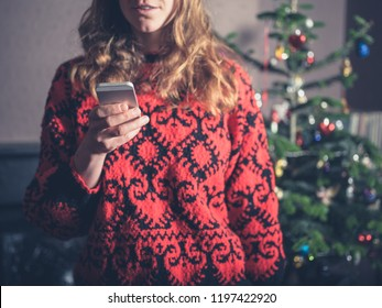 A young woman is using her smartphone by the christmas tree