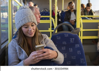 Young woman using her smartphone on the bus. There are other people sitting on the bus in the background.