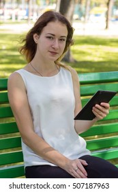 Young woman using her tablet in the park