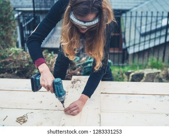 A young woman is using an impact driver outdoors in the winter