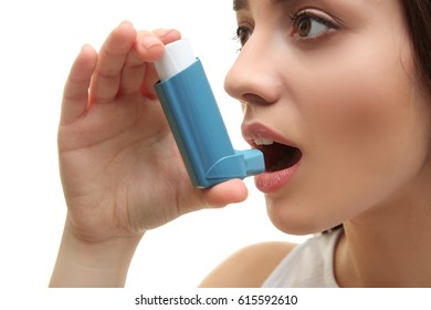 Young woman using inhaler during asthmatic attack on white background, closeup