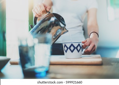 Young woman using kettle for make tea or black coffee on kitchen at room interior background.Women's hands pour water from a teapot into a cup. Blurred, flares effect