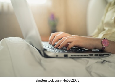 young woman using laptop in bedroom at home