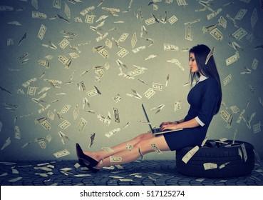 Young woman using a laptop building online business making dollar bills cash falling down. Beginner IT entrepreneur under money rain. Success economy concept