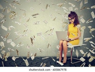 Young woman using a laptop building online business making money cash falling down. Beginner IT entrepreneur under dollar rain. Success economy concept