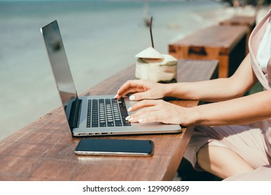 Young woman using laptop in cafe, near ocean, outdoor hipster portrait, freelance work, Bali, Thailand, smartphone, network, internet, island freedom, coconut, relax