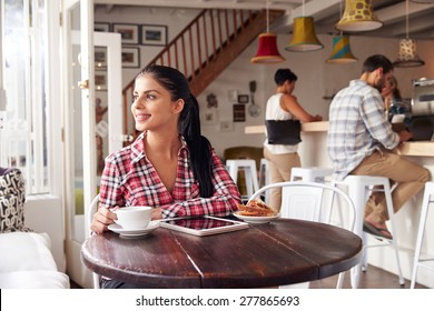 Young woman using laptop in a cafe