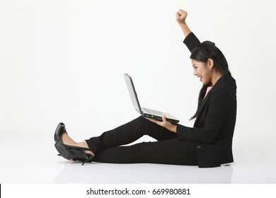 Young woman using laptop, cheering