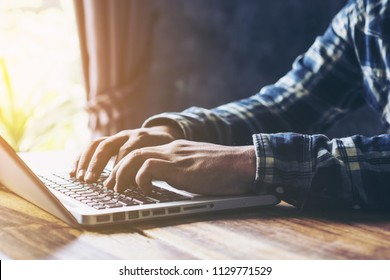Young woman using laptop computer. Male hand typing on laptop keyboard while sitting in coffee shop indoors, selective focus,