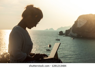Young woman using laptop computer at sunset in front of the sea on Ponza island coast, sitting on a wall with view of the ocean.