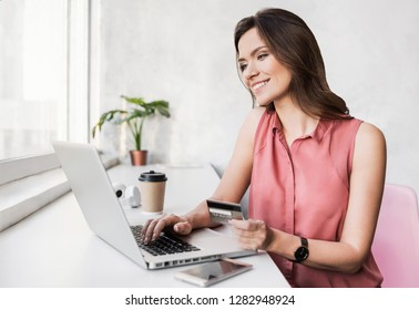 Young woman using laptop computer and holding credit card. Businesswoman or entrepreneur working. Online shopping, spending money, enjoying life concepts