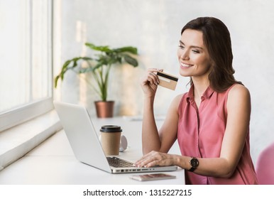Young woman using laptop computer and holding credit card. Businesswoman or entrepreneur working. Online shopping, e-commerce, spending money, enjoying life concepts