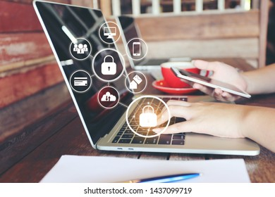 young woman using laptop computer and hand holding mobile smart phone with hologram in coffee shop, GDPR. cyber security and privacy concept