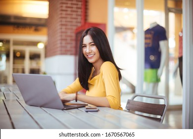 Young woman using laptop computer. Female working on laptop in an outdoor cafe.