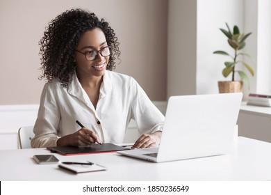 Junge Frau, die zu Hause einen Laptop benutzt. Studentenmädchen, das in ihrem Zimmer arbeitet