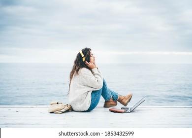 Junge Frau mit Laptop-Computer und hört Musik in der Nähe des Wintermeeres. Konzept der freiberuflichen Tätigkeit
