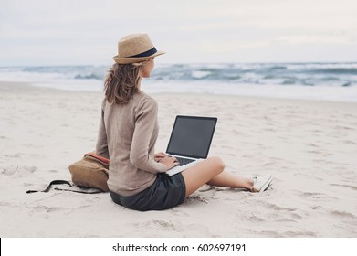 Young woman using laptop computer on a beach. Freelance work concept