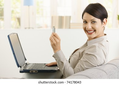 Young woman using laptop computer, showing up flash drive, smiling.?