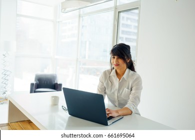 Young woman using laptop at desk, day, with window behind. young adult arabic pretty 20 years old