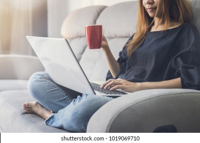 Young woman using laptop and drinking cofee on sofa at home