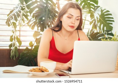 Young woman using laptop at home or in cafe