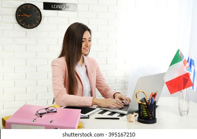 Young woman using laptop in the office of travel company