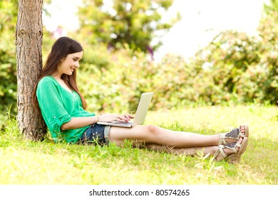 Young woman using a laptop on a park