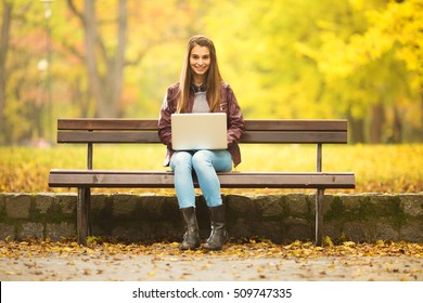 Young woman is using laptop in a park on a sunny Autumn day. She is smiling to camera