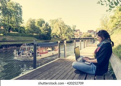 Young woman using laptop at a riverbank.