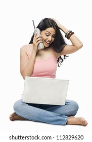 Young woman using a laptop and talking on a cordless phone