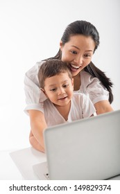 Young woman using laptop together with her little son