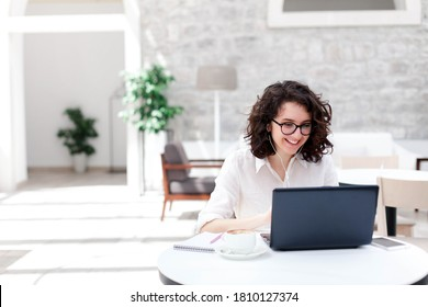 Young woman using laptop for webinar, video conference. Freelancer talking on virtual call and online meeting. Girl working in in coworking office. Connection, communication with social distance.