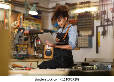 Young woman using a laptop in a workshop