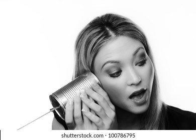 Young woman using a metal tin as a telephone