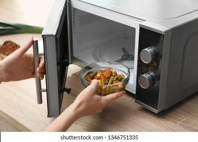Young woman using microwave oven on table in kitchen