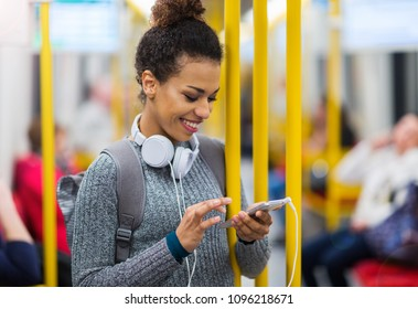 Young woman using mobile phone on subway
